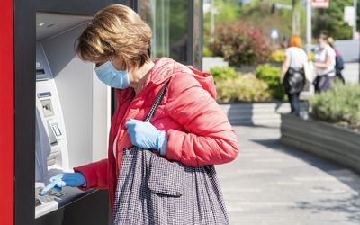 woman in mask and gloves at ATM