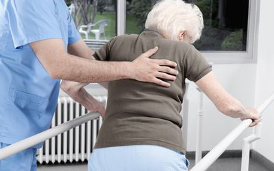 health worker assisting a woman walking in therapy
