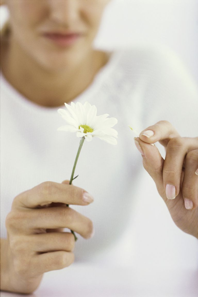 Woman picking petals off daisy, cropped