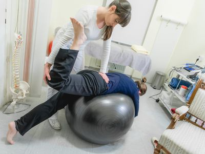 Woman going through assisted stretching with a physical therapist