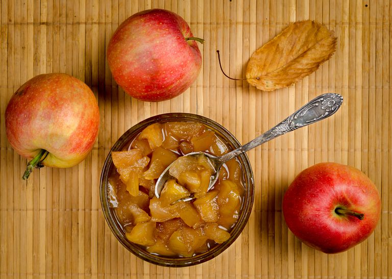 Apples and apple jam in a vase with a spoon