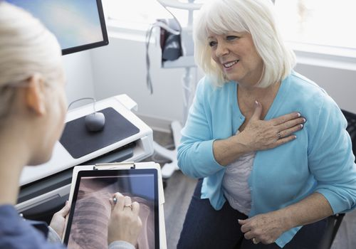 A woman talking to doctor about shoulder pain