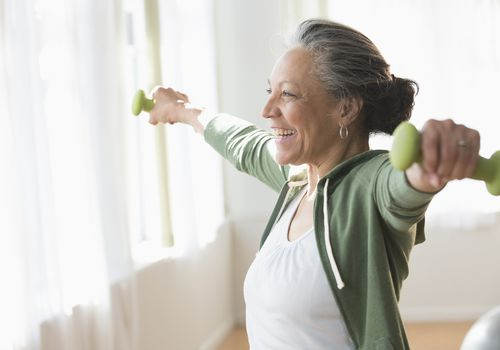 An older woman lifting weights in her living room
