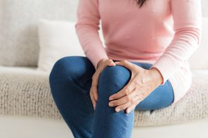 Midsection Of Woman Suffering From Knee Pain At Home