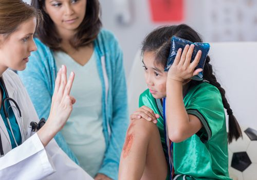 a girl with head injury being checked by doctor