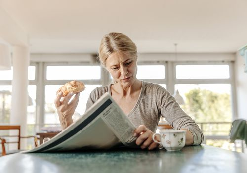 Woman at home having breakfast reading the paper