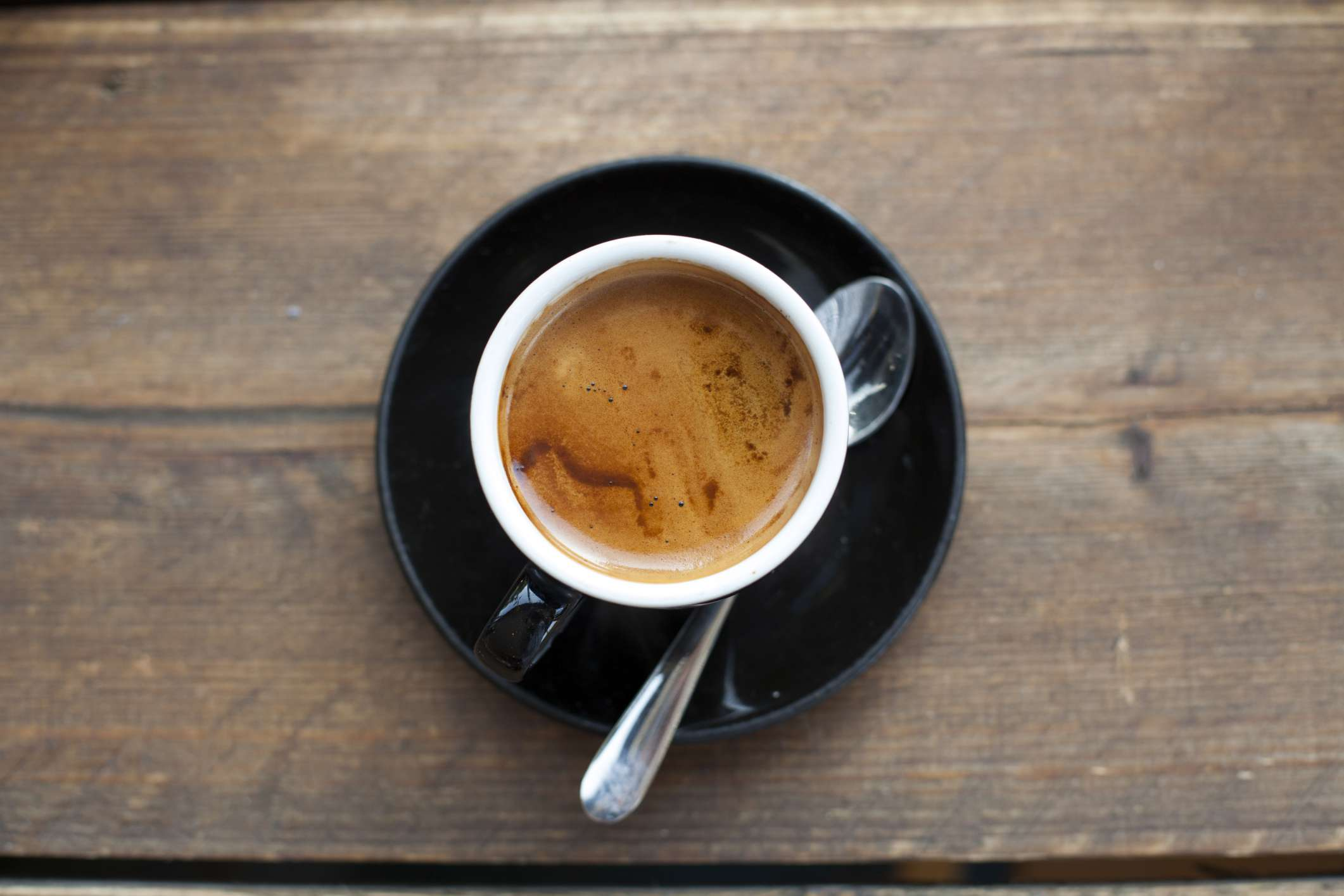 Cup of fleshly brewed espresso with saucer and spoon on wooden table