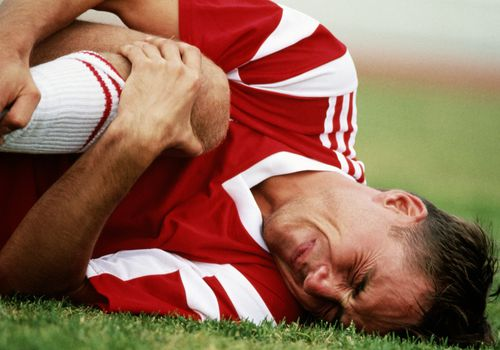 Soccer player in pain and holding his knee