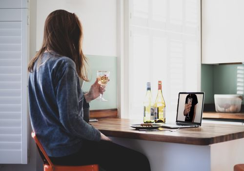 Woman having alcohol over a video call.