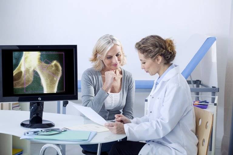 Woman speaking with her doctor and looking at paperwork after a bone scan