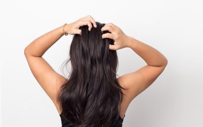 A view of the back of a person with long, dark hair, scratching their head