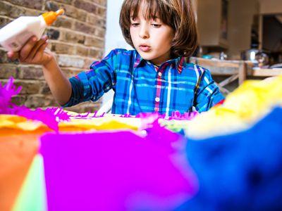 Boy spreading glue on crepe paper to make pinata
