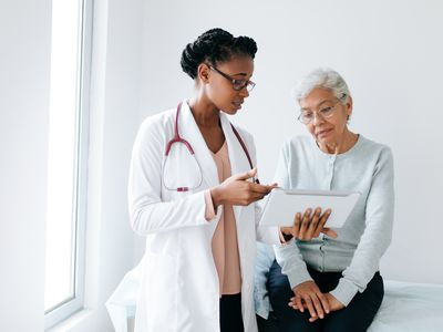 a doctor showing a patient her tablet