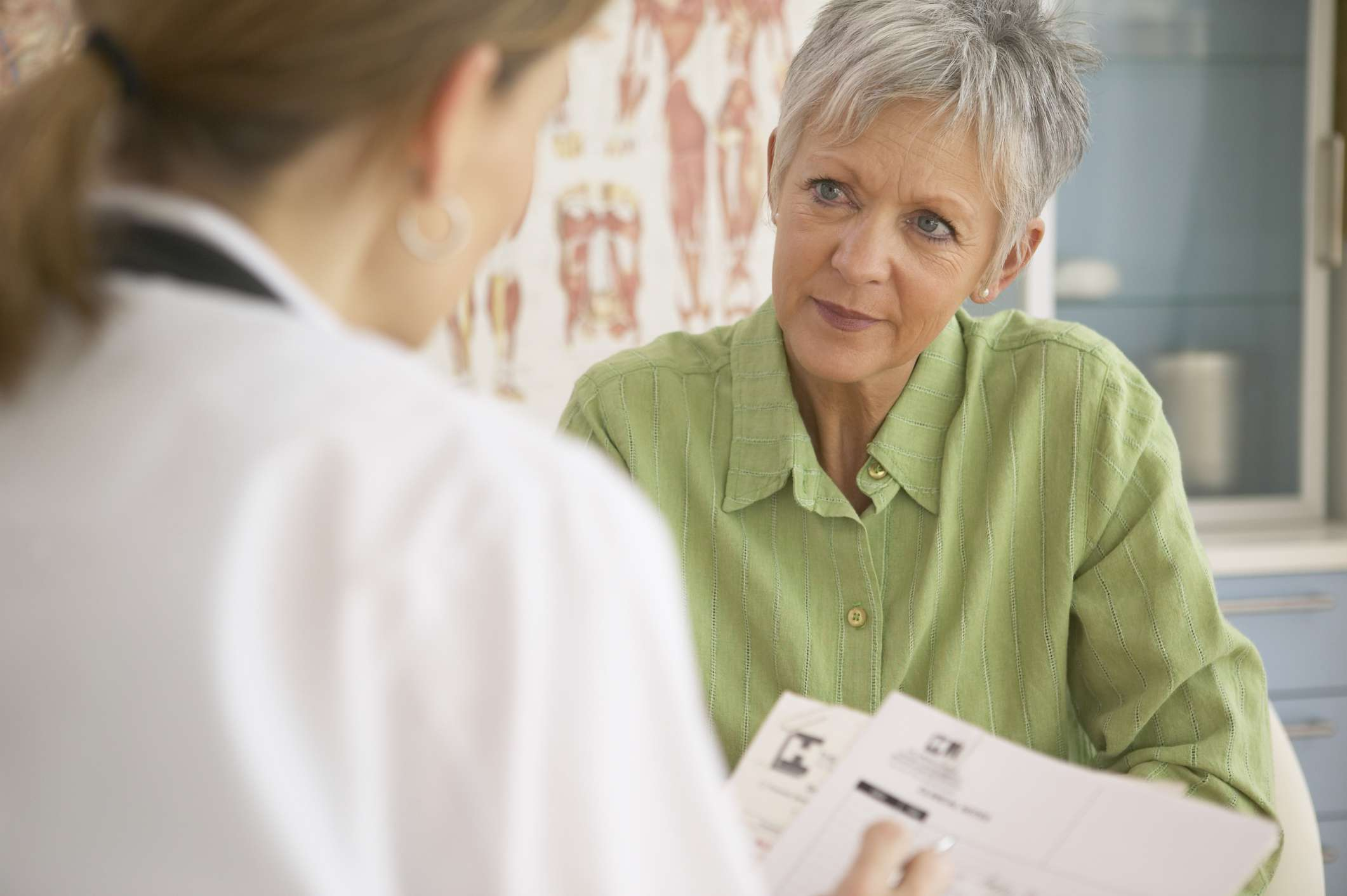 Female doctor talking to mature female patient