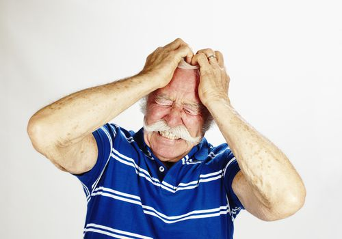 older man with mustache holding his head in frustration or pain, white background