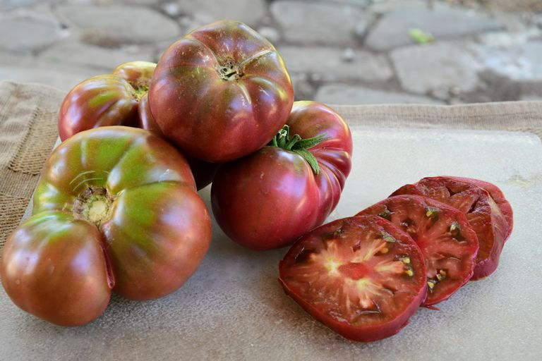 Group of fresh picked and sliced Cherokee Purple heirloom tomatoes