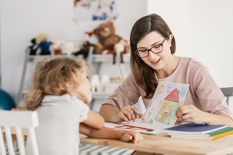 Woman showing drawing to small girl