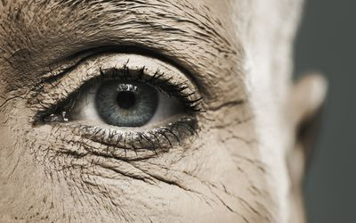 Mature woman with dried mud around the eye area.