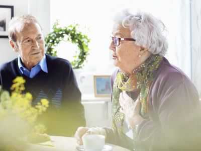 Senior woman talking to friends at breakfast table in nursing home
