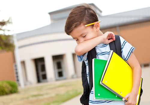 Young boy at school coughing into his arm