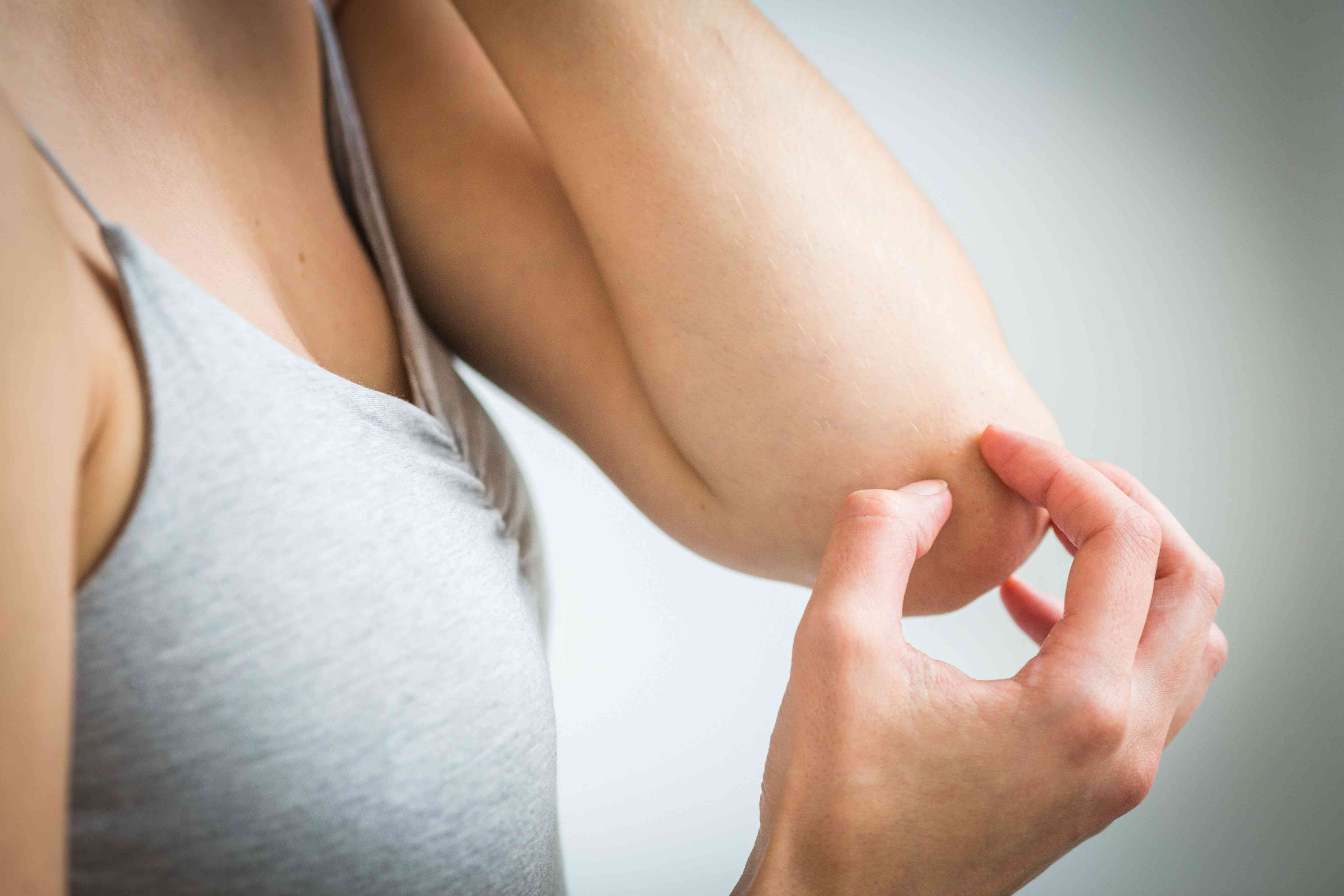 Woman touching arm near elbow joint