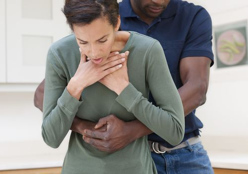 man doing heimlich maneuver on woman