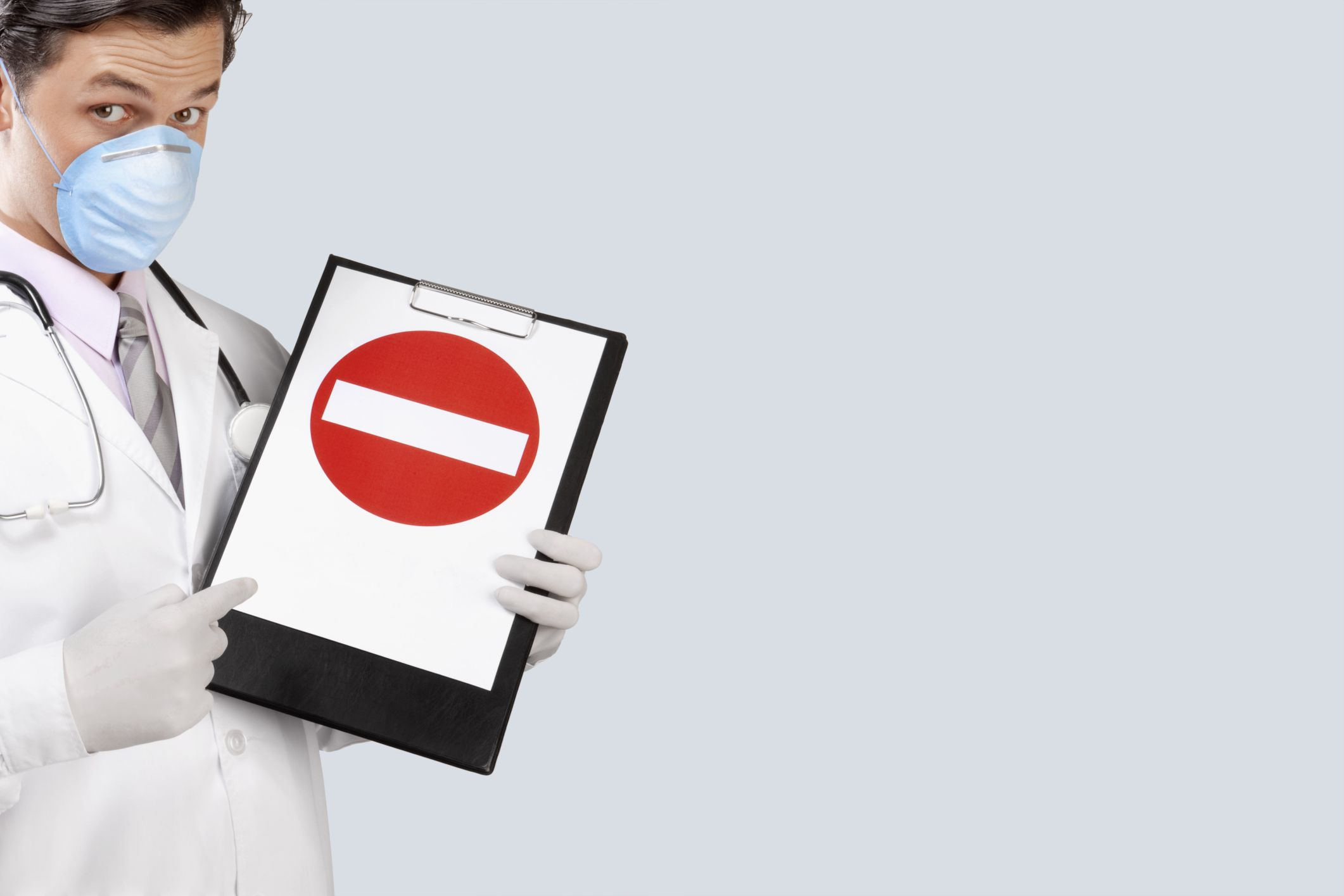 Doctor with face mask holding a clipboard facing the camera that bears an image of a minus sign inside a red circle