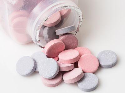 Antacid tablets spilling out of a bottle