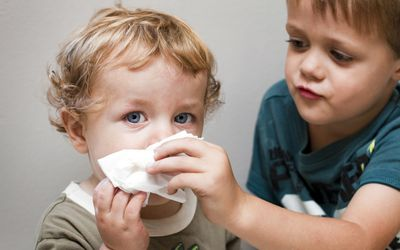 Older boy helping a younger boy blow his nose