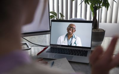 A woman has a telehealth appointment on her laptop with an androgynous Black doctor.