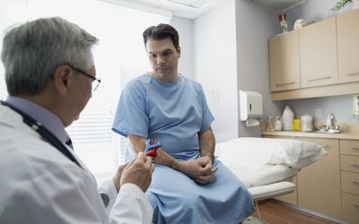 Doctor explaining model to patient in examination room