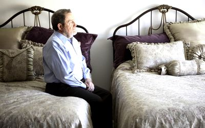 Man sitting on a bed staring ahead