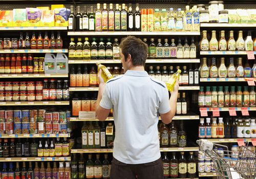 Man deciding between cooking oils in grocery store