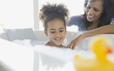Mother bathing daughter in bathtub