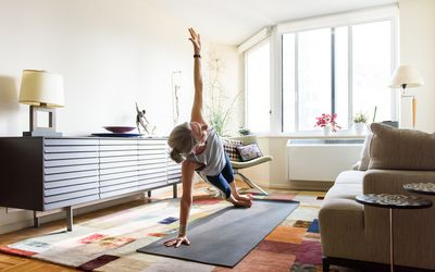 Woman holding side plank fitness pose in her home on yoga mat
