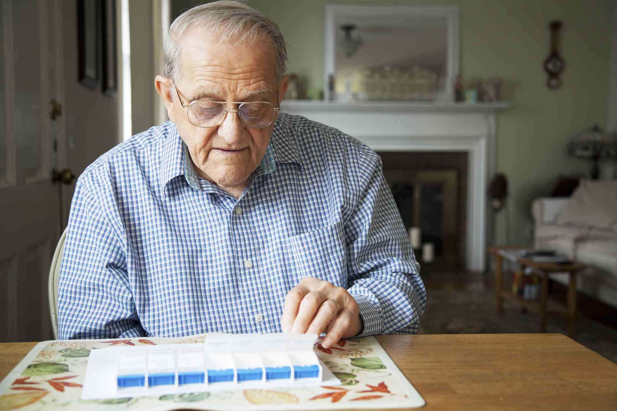 elderly main looking at pill box