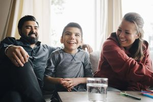 Smiling parents looking at autistic son while sitting on sofa in living room