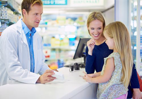 A pharmacist talking to a woman and her daughter