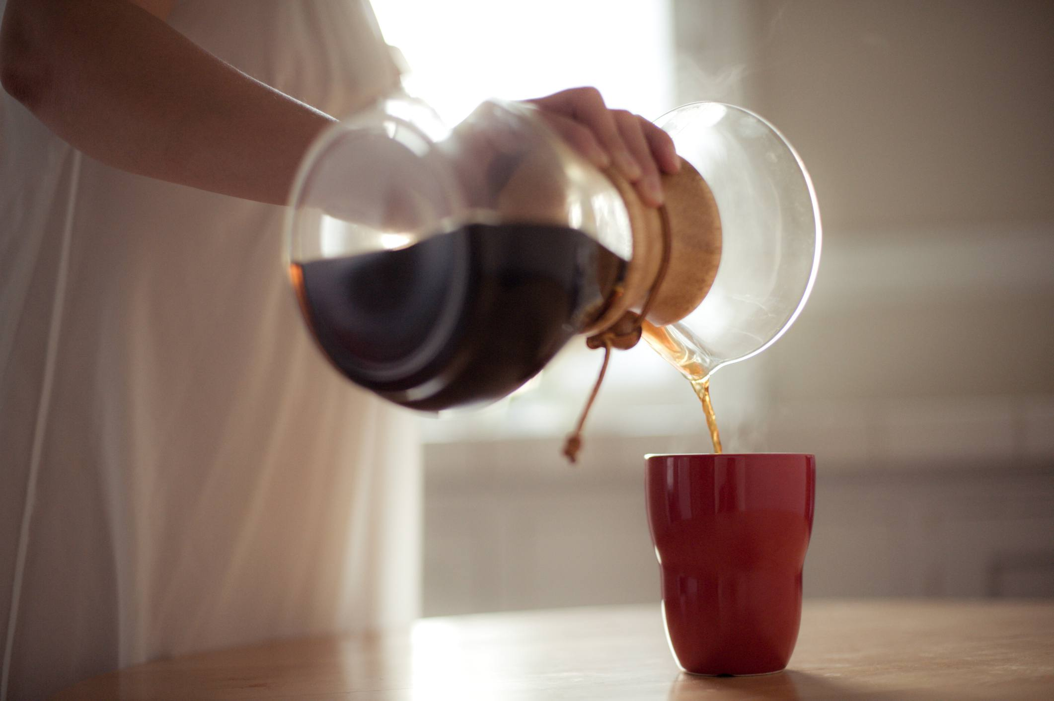 Woman pouring coffee from pour over coffee maker into red cup