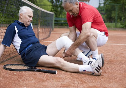 senior man wrapping another senior man's knee on a tennis court
