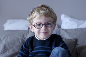 Young male child with blonde hair, blue eyes, and glasses smiling.