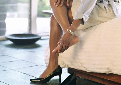 Woman taking off high heels, rubbing feet, side view, low section