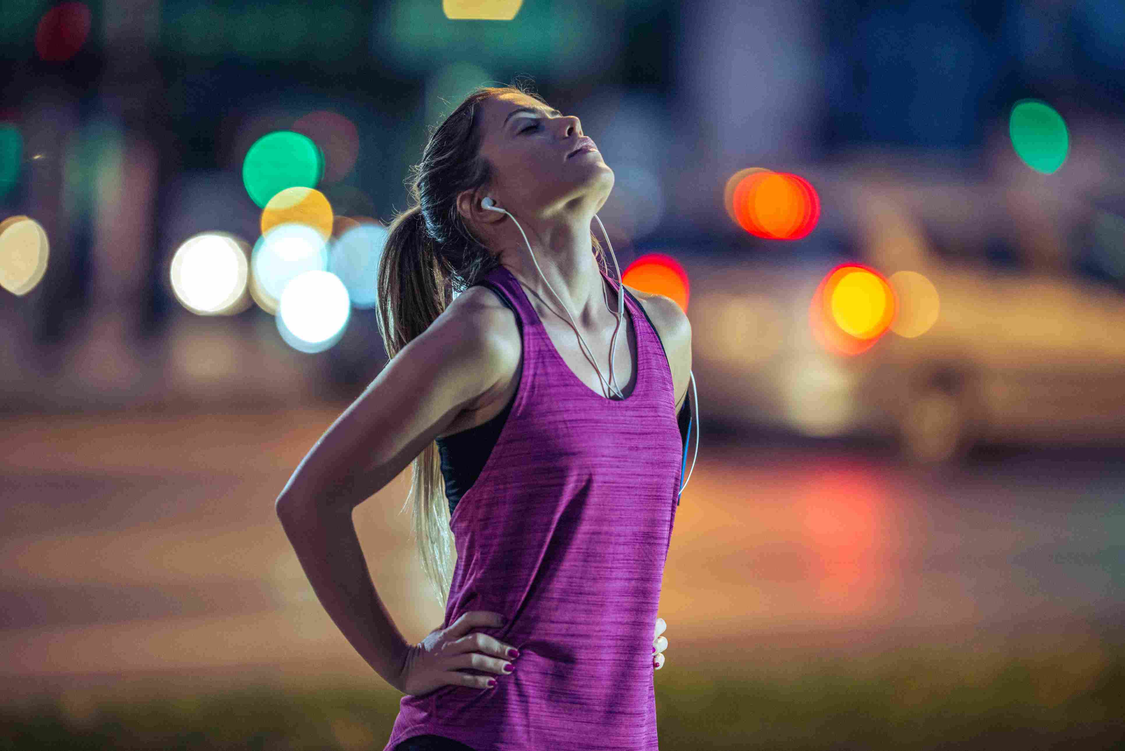 A woman catching her breath after a run, night scene