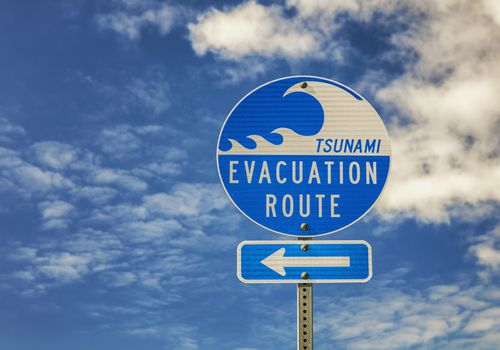 tsunami route sign with a blue sky and clouds in the background