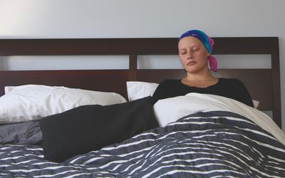Cancer patient sleeps in bed - stock photo Taken from foot of bed