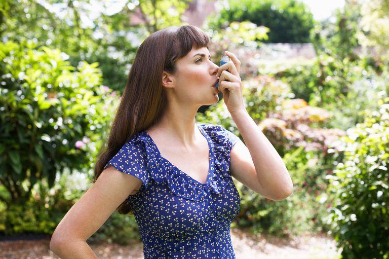 Woman using Asthma inhaler in garden