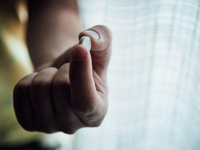 Hand holding a pill