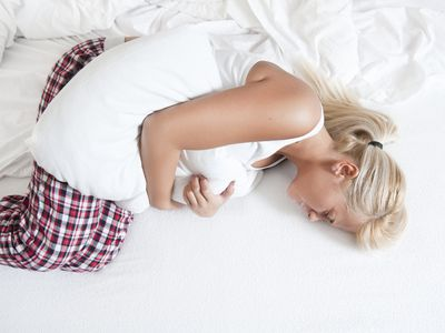 woman curled up in pain on a bed