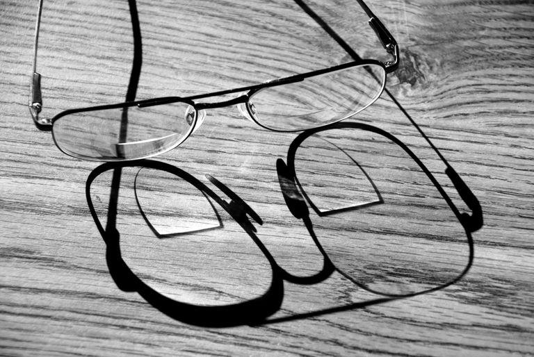 bifocal glasses sitting on a wooden table