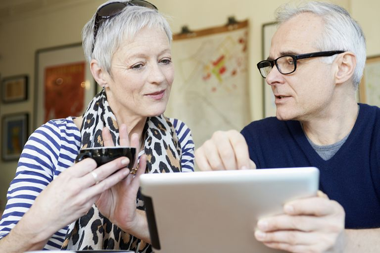Mature man and woman in cafe with digital tablet